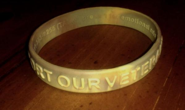 A desert camouflage bracelet for veterans from the VA with crisis support information imprinted on the inside surface.