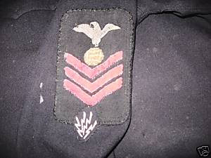 This EM/1c rating badge dating from the WWI timeframe shows the four electrical sparks of the radio operator/technician distinguishing mark affixed directly below the bottom chevron.