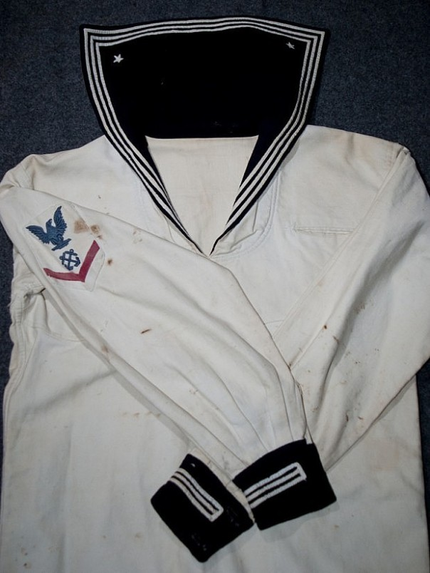 I have the privilege of owning this 1905-1913 coxswain dress white uniform. Note the blue wool cuffs and collar flap and the three-stripe white piping affixed. The flap also has two white stars directly embroidered to each corner.