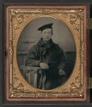 This Civil War-vintage tin type photograph shows a sailor wearing his dress blue jumper, blue neckerchief, and flat hat (source: Library of Congress).