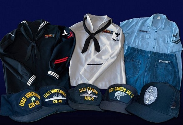 This collection of uniforms shows four official shipboard navy ball caps, authorized for wear with utility uniforms (such as the now-defunct dungaree set on the right). Note the UIM patch on the right sleeve of the dress blue uniform jumper.