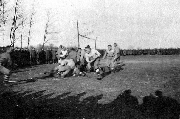From my uncle's WWI photo album, this photo shows the gridiron surrounded by soldiers in full uniform. The action on the field is quite compelling as the ball carrier runs to the left for the goal line. Note the makeshift goal post in the background.