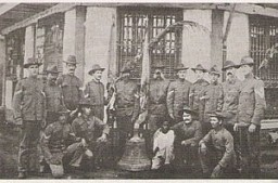 The American survivors of the attack pose with one of the captured church bells used by Filipino insurgents to coordinate the attack against the Americans.