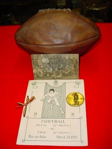 A fellow collector's AEF football memorabilia - a program – 36th Division (1st Army) vs 7th Division (2nd Army) March 21, 1919; a football from a game between the 77th Division vs 81st Division teams; Football Championship Coin | First Prize – 86th Division.(source: Mark McCaffrey – Falls Creek Military Collectibles)