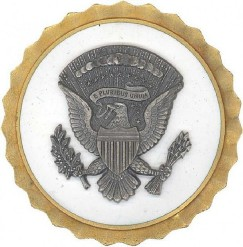 The obsolete White House Service Badge features a natural metal seal on the white field. When this bade was retired in 1964, it was replaced with the Presidential and Vice Presidential Service Badges.