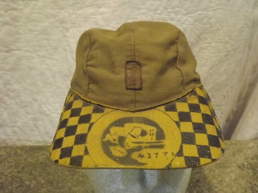This khaki aviator's ball cap is an oddity with this artwork on the bill. A sewn-on rank insignia adorns the front panel (source: eBay Image).