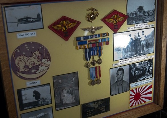 "This display features WWII USMC ace, Major Bruce Porter's decoration and medals with his naval aviator ""wings of gold."""