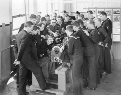 Enlisted sailors learn about the PT Boat engines at the The Packard Marine Engine School. Note the sailor (third from the left) with the PT Boat patch on the forearm of his right sleeve (image source: pt-king.gdinc.com),